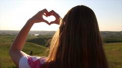 Beautiful woman, hands making heart shape gesture holding sun flare Stock Footage