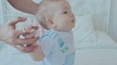 Father help his baby son to stand on the bed Stock Footage