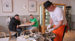 Chef opens oysters for visitors to the restaurant. - stock footage