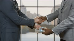 Businessmen with money shake hands. Stock Footage