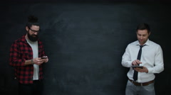 4K Happy casual businessmen using interactive technology together on chalkboard Stock Footage