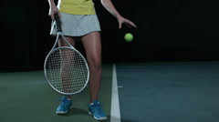 A woman bounces a ball on a tennis court in slow motion before serving Stock Footage