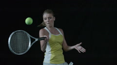 Woman hitting tennis ball with racquet - head on, eye level in Slow Motion Stock Footage