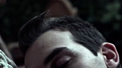Putting out a cigarette on another man forehead - stock footage
