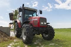red tractor with tedder - stock photo