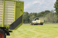 Forage harvester and transport of grass with tractor and a loader wagon Stock Photos