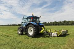Pasture mowing with blue tractor and mower Stock Photos