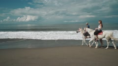 Horse riding instructor leading a horse with a woman on a beach (white horses) Stock Footage