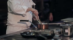 chef at the stove with a spoon stirs - stock footage