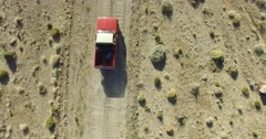 Aerial top scene of off road car in a dirt road on a desertic, dry, rocky, sand Stock Footage