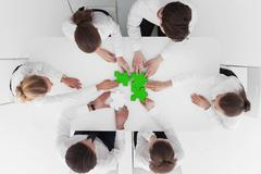 Business people assembling puzzle Stock Photos