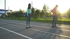 Man and woman riding on hoverboard Stock Footage