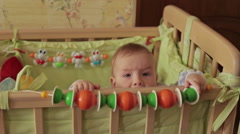 Cute baby boy standing in crib looking at camera at home - stock footage
