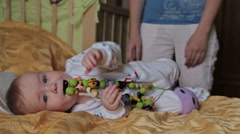 Baby boy lying on bed smiling and playing toys Arkistovideo