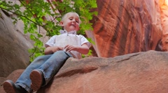 Red Rock Slot Canyon With Kids On A Big Rock. Stock Footage