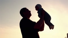 Father raises child silhouette at sunset Stock Footage