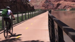 Bicycle rider on Bike trail along the Colorado River Stock Footage
