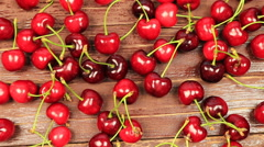 A man's hand take red ripe cherry on wooden table Stock Footage