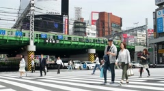 Tokyo - People on crosswalk with train passing by. Shinjuku. 4K resolution Stock Footage