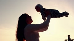 Mother raises child silhouette at sunset Stock Footage