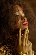 Elegant serious African or black American woman wearing gold makeup and acces Stock Photos