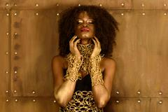 Beautiful young African woman with gold earthy makeup and necklace, laying ha - stock photo