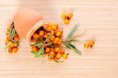 Top down of berries are scattered out of a ceramic pot on a wooden background Stock Photos