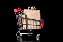closeup shopping cart with paper bags is isolated on black background - stock photo