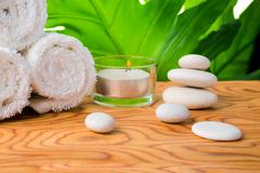 Beautiful spa setting of stones, candle, rolled white towels and green leaf o Stock Photos