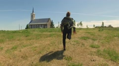 Girl running outdoor. Green summer landscape. Church at background. Stock Footage