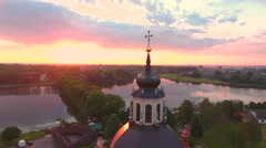Aerial View.Flying over the dome of the church with a cross in the city at sunse Stock Footage