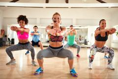 Female instructor doing exercises for shaping breech and thighs Stock Photos