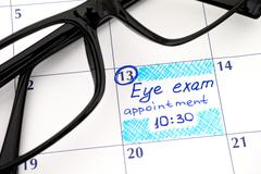 Reminder Eye exam appointment in calendar with glasses - stock photo