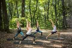 Group youngsters doing body balance in nature Stock Photos