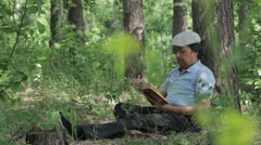 Man reading a book on nature. Stock Footage