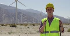 Wind farm technician jump starts wind turbines 4K Stock Footage