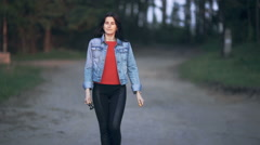 Beautiful girl walking in the park at sunset Stock Footage