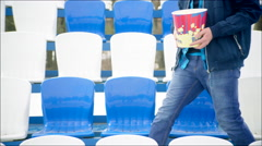 A guy sat on the tribune with popcorn bucket - stock footage
