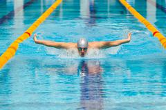 Dynamic and fit swimmer in cap breathing performing the butterfly stroke Kuvituskuvat