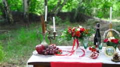 Boho-chic wedding style, table with fruits and candles in the forest. Stock Footage