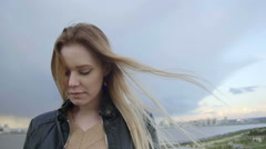 cute girl with long blonde hair with blue yeys in leather jacket straightens - stock footage
