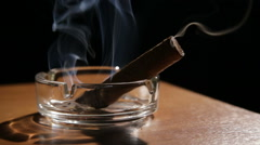Smoking cigar in an ashtray - stock footage