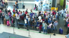 Airline passengers waiting in line to check in at the airline counter. - stock footage