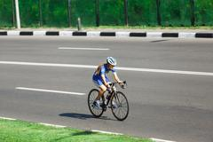 Female cyclist rides a racing bike on road Stock Photos