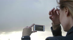 girl with long blonde hair in leather jacket straightens hair photographing the - stock footage