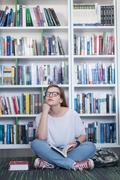 famale student reading book in library - stock photo