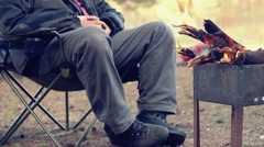 Tourist sitting on camp chair near campfire. Outdoor recreation Stock Footage