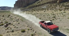 Aerial scene of car traveling on dirt road, dry, rocky, landscape. Monumental sc Stock Footage