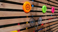 Flying saucers and volleyball racket mounted on a wall of boards - stock footage