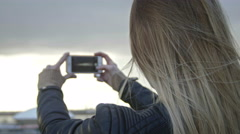 cute girl with long blonde hair in leather jacket straightens hair photographing - stock footage